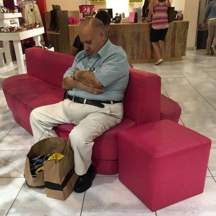 Hombre dormido en sillón rosa de tienda