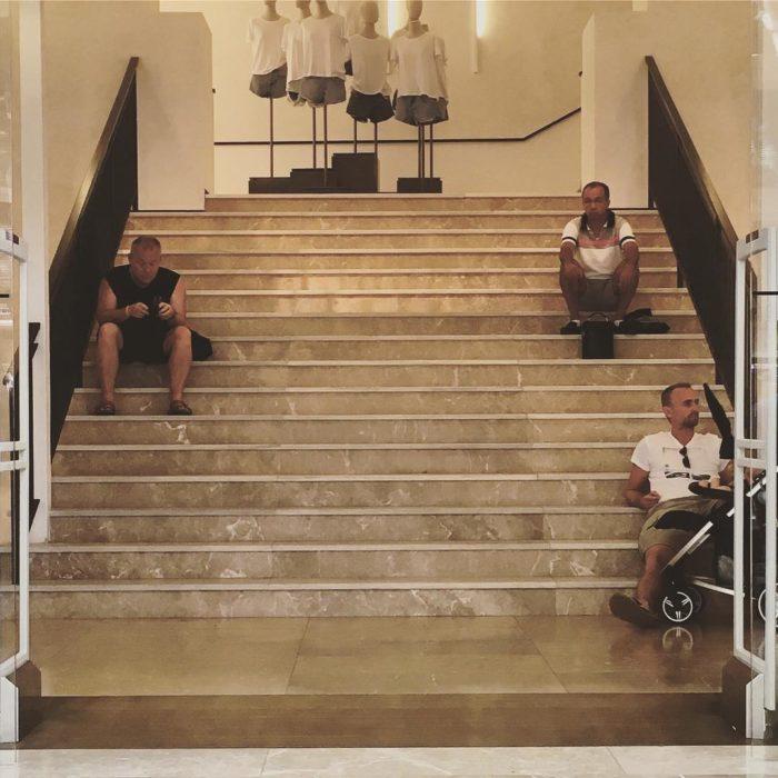 Tres hombres esperando en escaleras