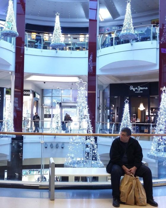 Hombre esperando a su espossa en centro comercial