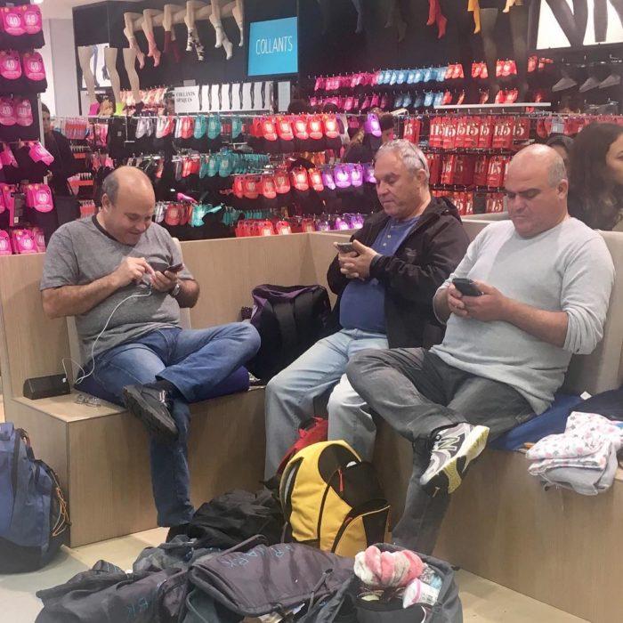 Hombres con el celular mientras sus esposas compran