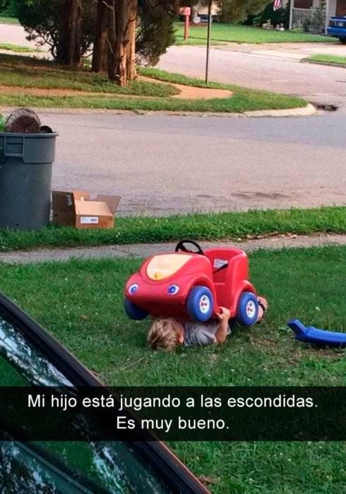 Niño debajo de su coche de juguete