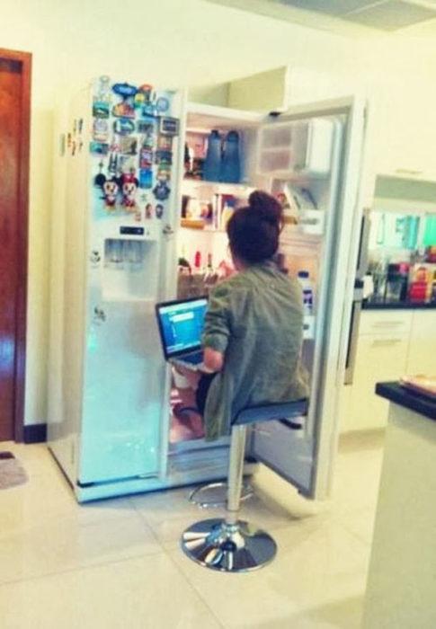 Chica con la computadora en las piernas sentada frente al refrigerador