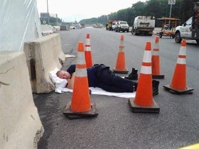 Policía dormido en la calle entre conos de tráfico