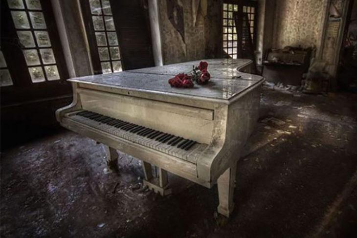 Piano abandonado con flores encima de el