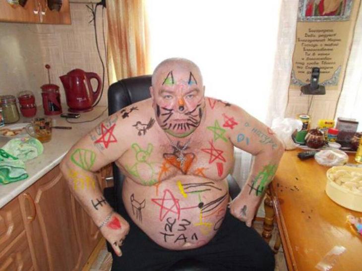 hombre con muchos dibujos hechos por niños en si cuerpo