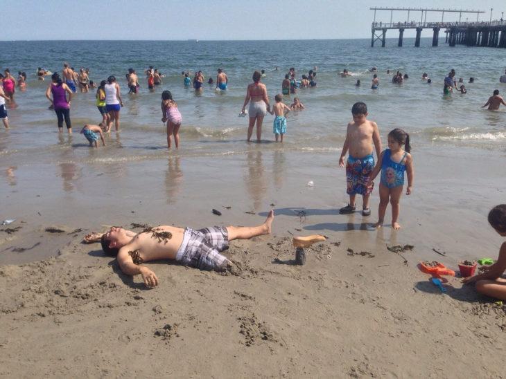 Hombre con pierna amputada hace broma en la playa