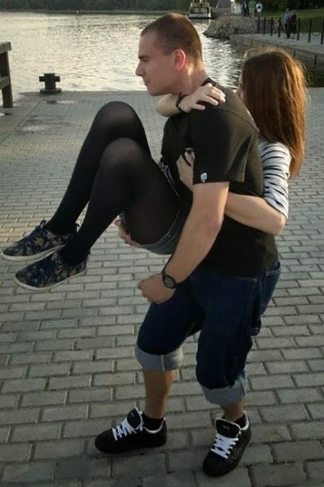 hombre cargando a mujer pero por la posición de la imagen parece lo contrario