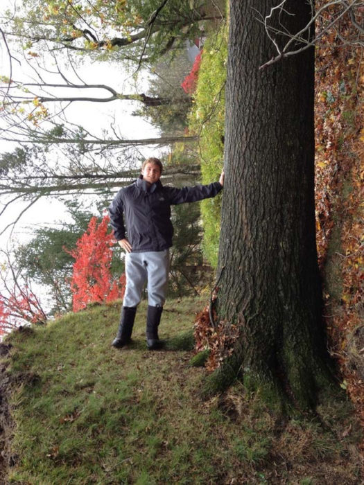 Joven posando en un árbol caído y simula fondo distrocionado