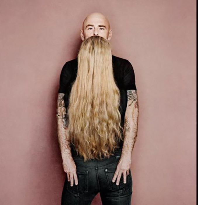 Chica enfrente de joven hace ver como si tuviera una larga barba