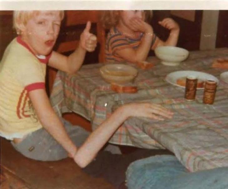 niño que parece tener brazo largo pero es otro niño abajo de la mesa que hace que así lo parezca