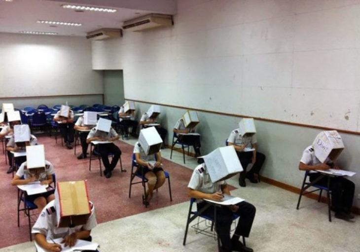 Maestro pone cajas en cabezas de alumnos para que no se copien