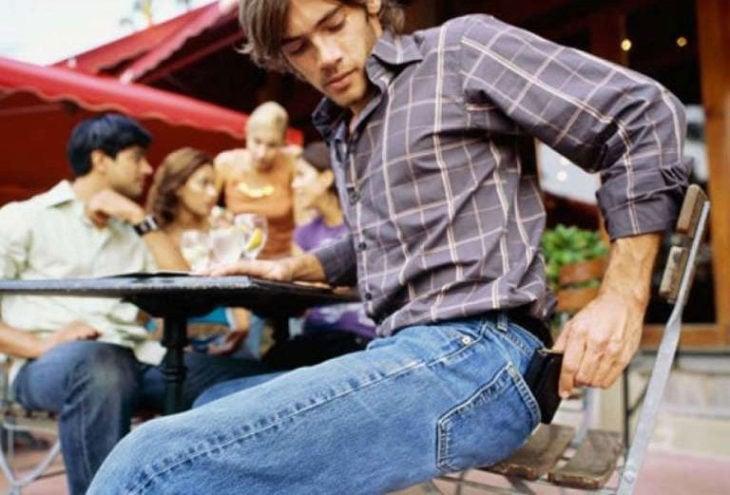 Hombre sentada sacando su billetera de su bolsillo trasero