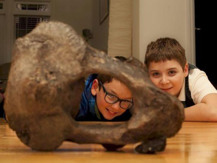 niños viendo un hueso de mastodonte