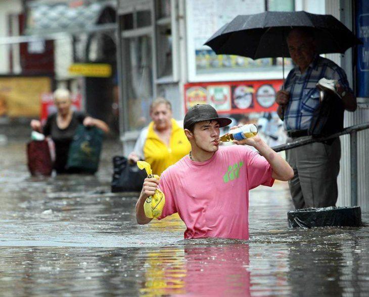 hombre bebiendo cerveza en medio de inundación