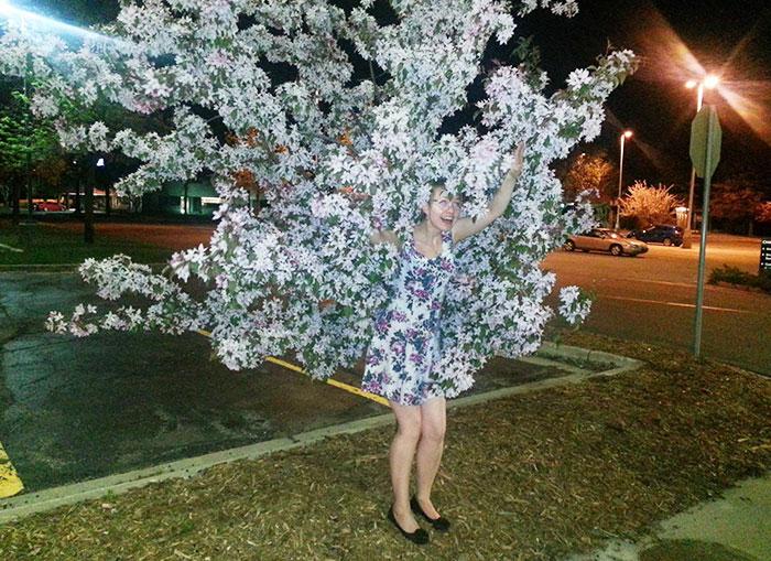Mujer con vestido de flores escondida en árbol