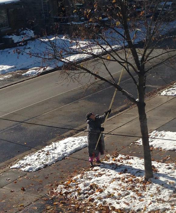 vecina tirando las hojas del árbol