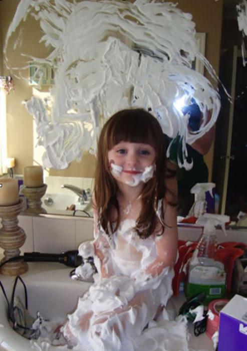 Niña llena espejo con espuma