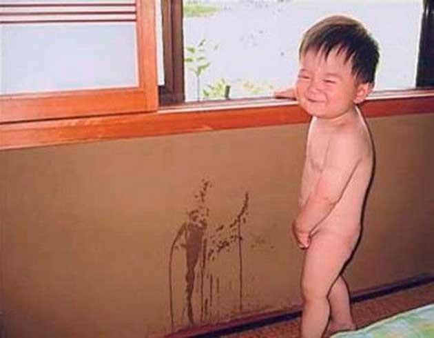 Niño orinando en la pared