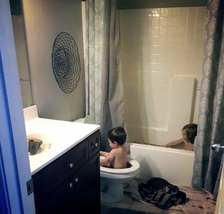 Niño tomando el baño en el escusado