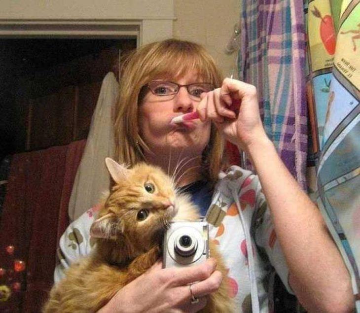señora cepillando sus dientes, cuidando al gato selfie