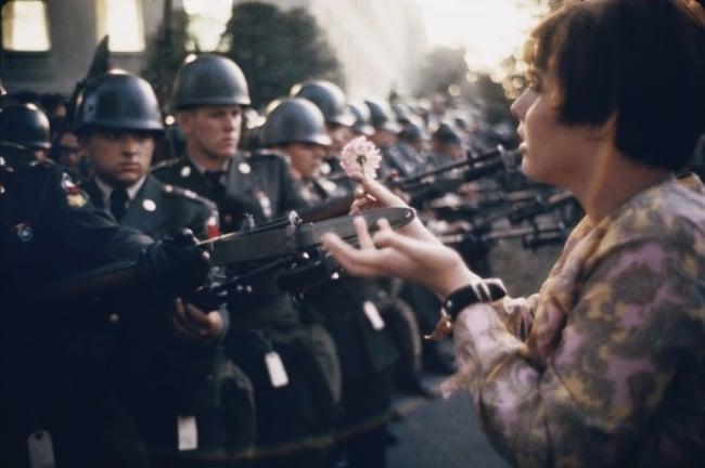 Manifestante pone flores en armas
