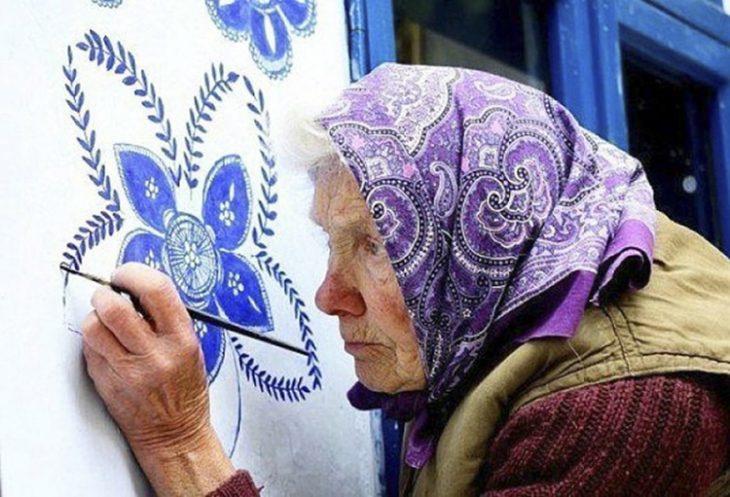 Anciana pinta casa a mano