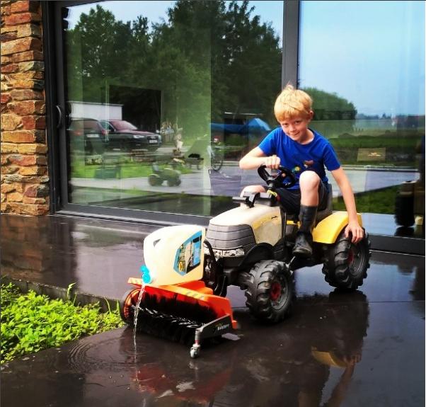 Niño ingenioso limpiando el patio