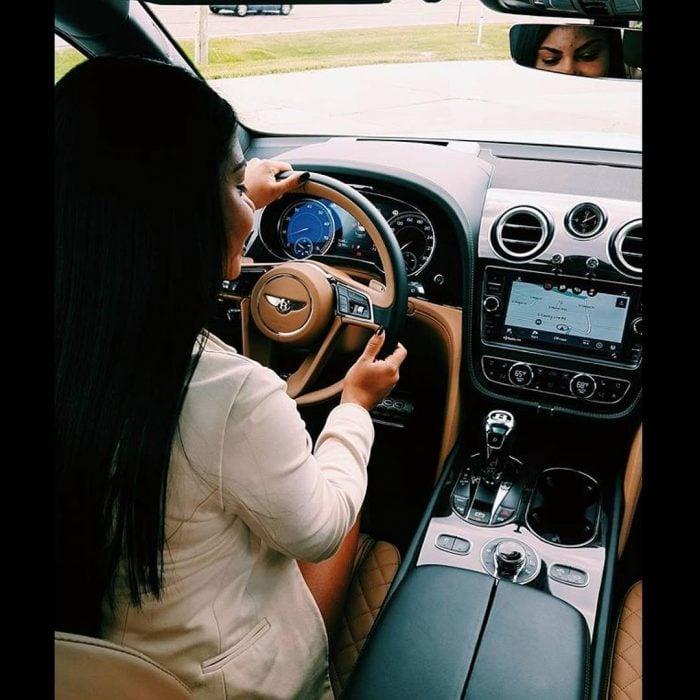 mujer manejando coche de lujo