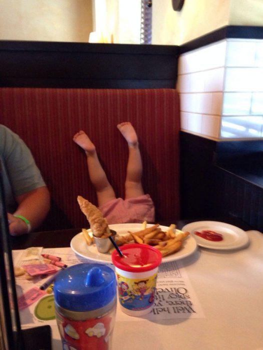 niña restaurante pies arriba