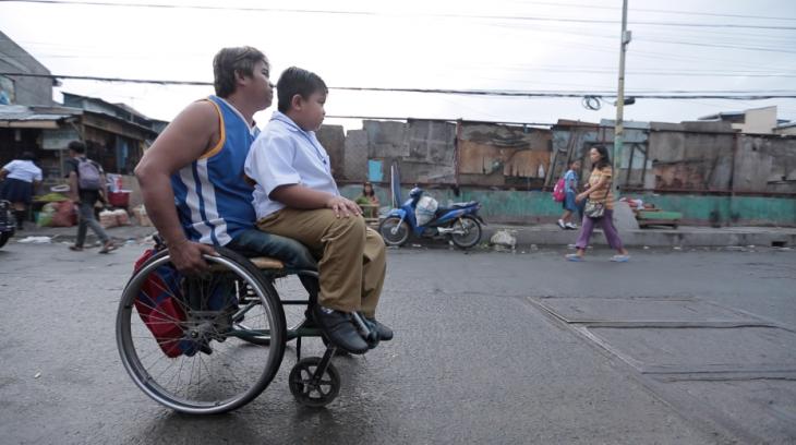 Niño rumbo a la escuela en silla de ruedas