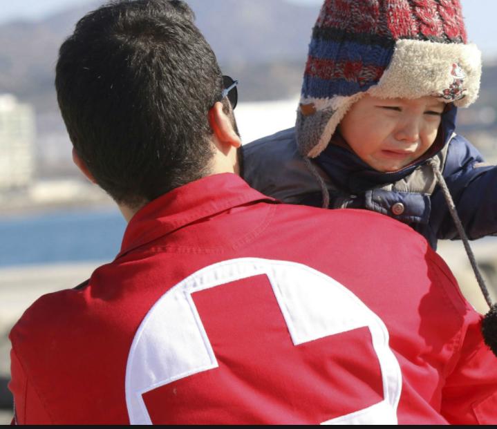 hombre con chaqueta roja cargando a niño