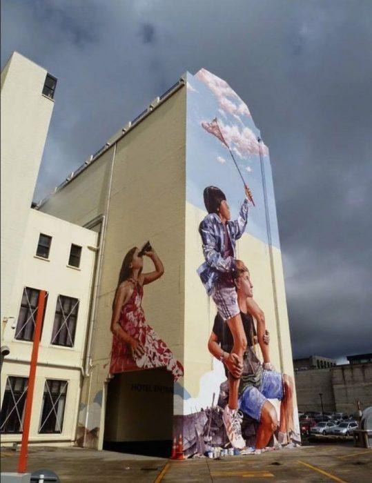 edificio con pintura de tres personas gigante