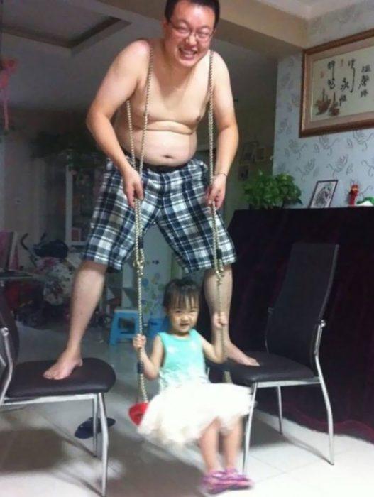 hombre con bermuda a cuadros columpiando a una niña