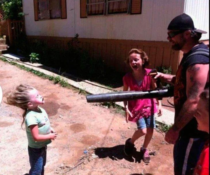 padre jugando con niñas arrojando aire