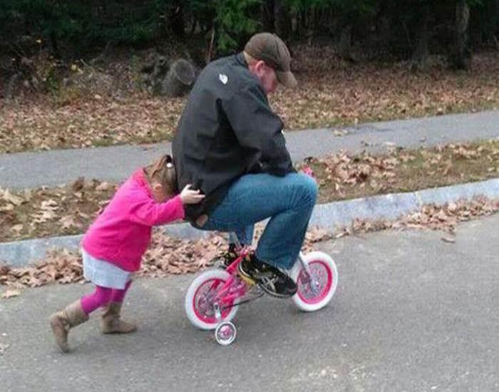 niña empujando a u hombre en bicicleta