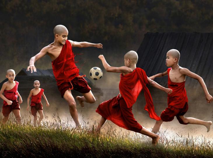 niños vestidos de rojo jugando con un balon