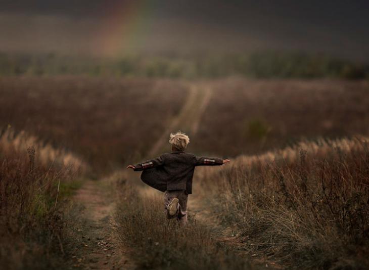 niño corriendo por la pradera