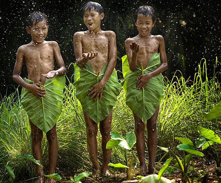 niños se tapan con hojas de palmeras