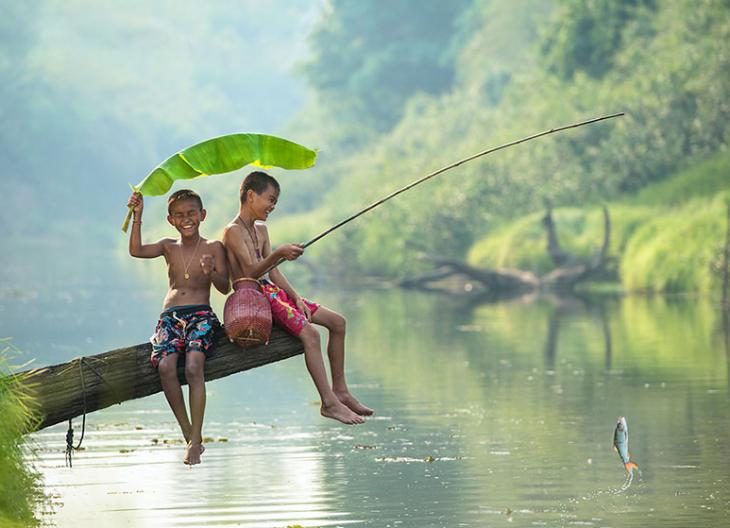 dos niños pescando en un rio