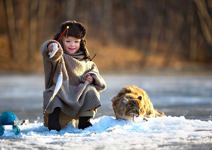 niño pescando en el hielo un gato a su lado
