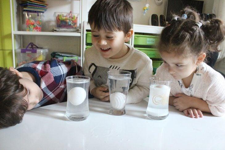 niños mirando un experimento en vasos con huevos