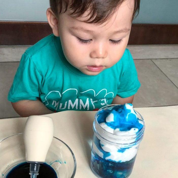 niño frente a un experimento de nube y lluvia