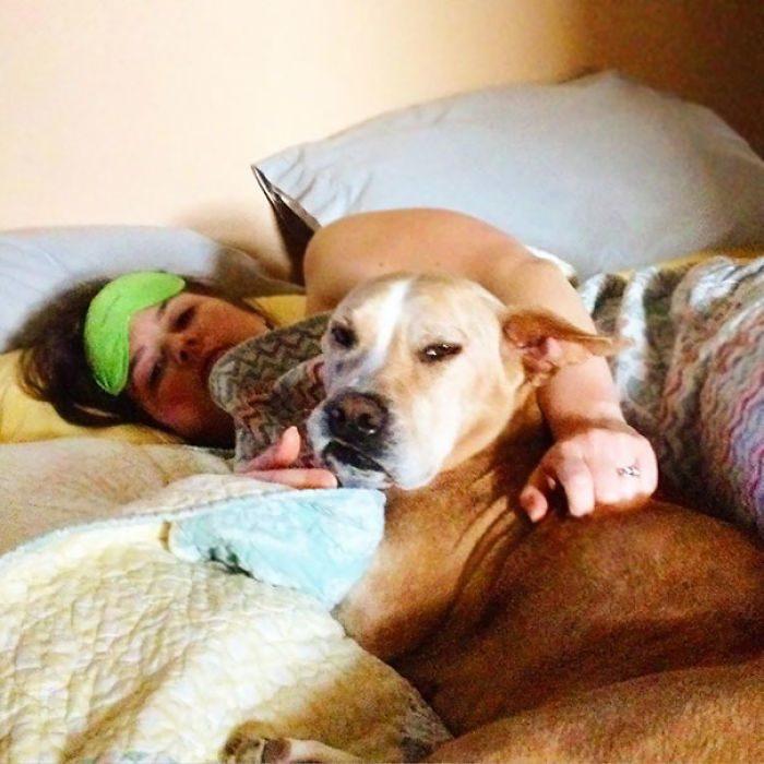 mujer recostada con un perro al lado