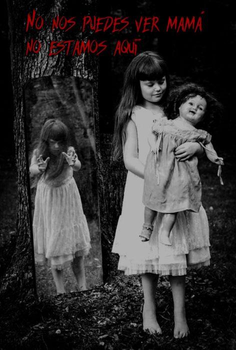 Imágen detenobroza de una niña, una muñeca y un espejo