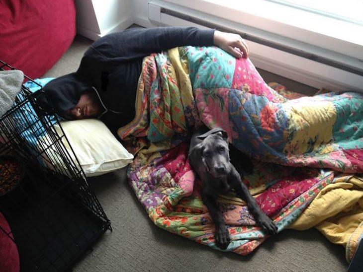 hombre y perro recostados en el suelo