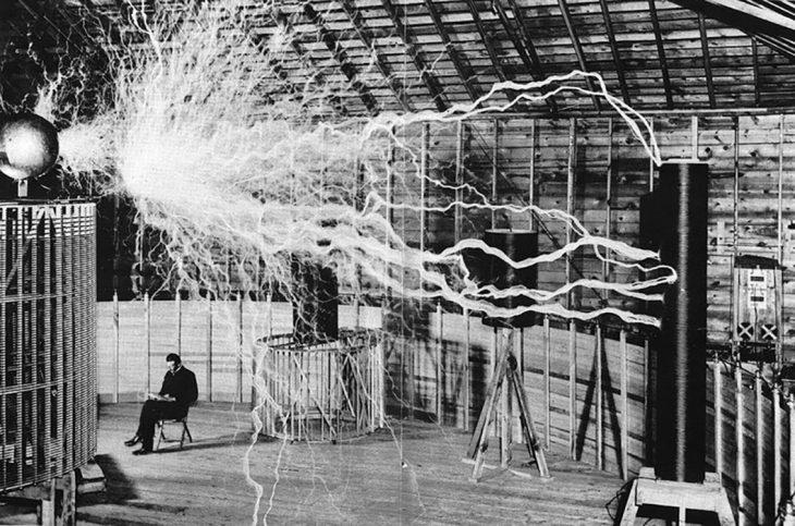 Nikola Tesla sentado en su laboratorio con la conocida Bobina de Tesla
