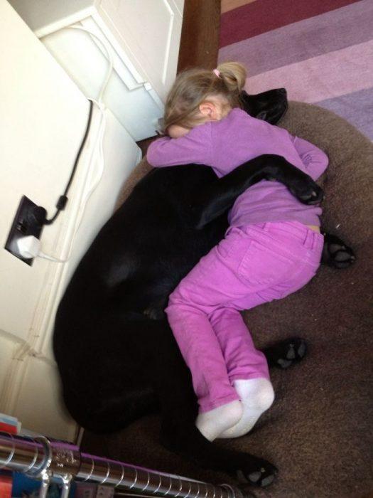 perrito abrazando a niña