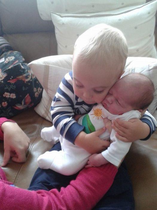 bebé abrazando a un recién nacido