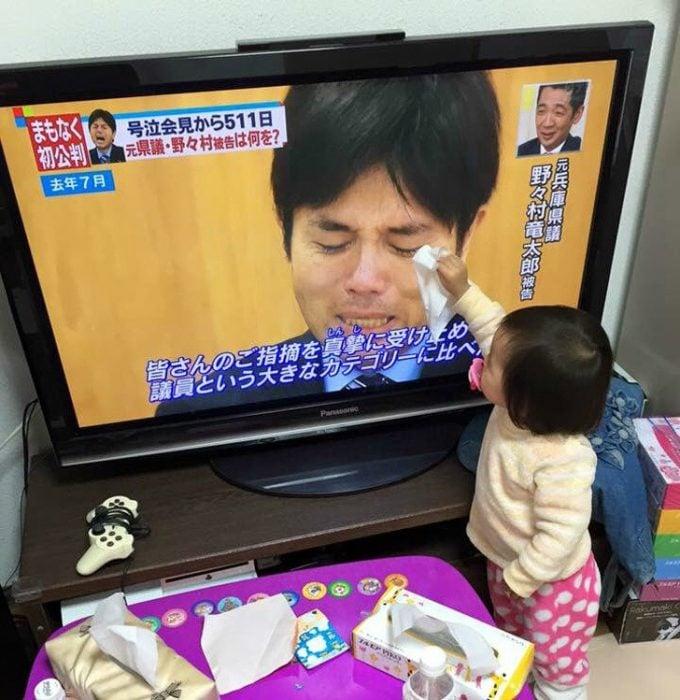 niña consuela a persona en la tele