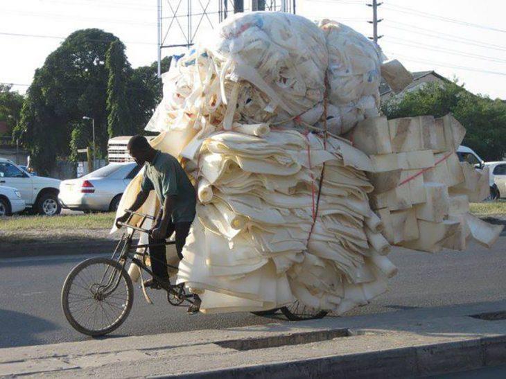 chico con una gran carga de esponjas en su bicicleta